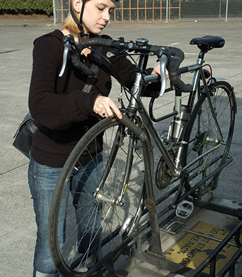 Photo of bicyclist placing bike on bus rack